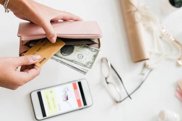 Mani di giovane donna che tiene portafoglio in pelle beige nudo con banconote da un dollaro e carta di plastica sopra smartphone e occhiali da vista sulla scrivania Foto Premium