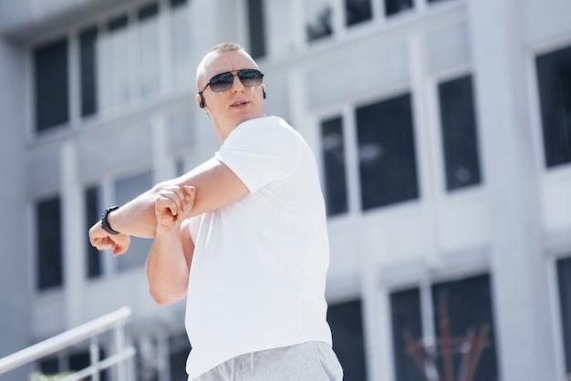 Un bell'uomo fitness in un abbigliamento sportivo, facendo stretching mentre si prepara per un serio esercizio fisico nella città moderna Foto Premium