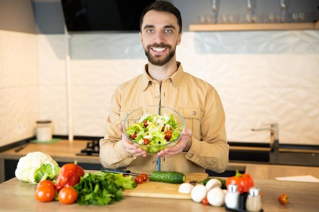 Bel ragazzo con barba e bel sorriso sta mostrando la sua preferenza uno stile di vita sano e sta mangiando cibo fresco. Foto Premium