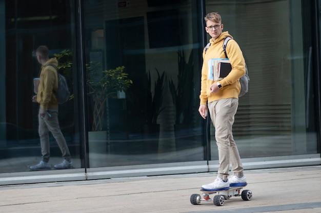 Bel ragazzo, giovane uomo, hipster, studente o allievo in bicchieri sul suo viso cavalcando skateboard elettrico urbano moderno con zaino, libri e libri di testo. trasporto ecologico, concetto di tecnologia. Foto Premium