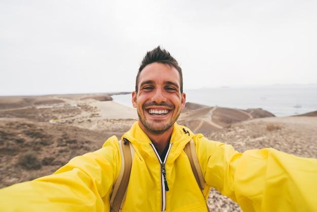 Uomo bello escursionista sorridente prendendo un selfie sulla cima di una montagna. Foto Premium