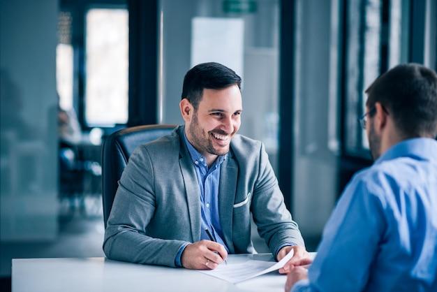 Documento di firma del cliente maschio bello su una riunione con l'agente immobiliare. Foto Premium