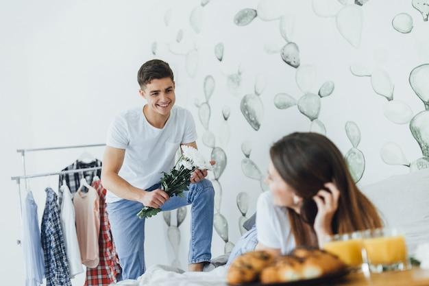 Un bell'uomo ha portato dei fiori nel letto a sua moglie. Foto Premium