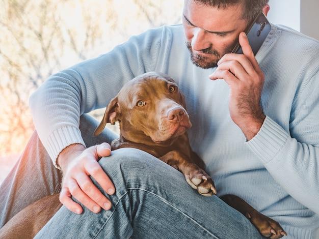 Bell'uomo e un cucciolo affascinante. avvicinamento Foto Premium