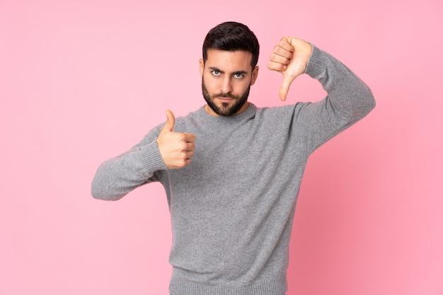 Uomo bello sopra la parete isolata che fa segno buono-cattivo. indeciso tra sì o no Foto Premium