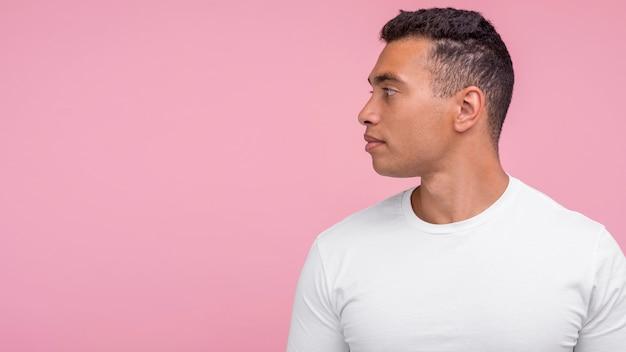 Uomo bello che propone dal profilo con lo spazio della copia Foto Premium