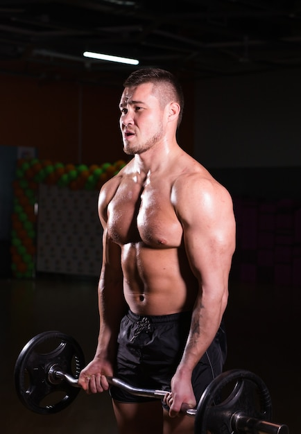 Uomo atletico bello potere con bilanciere che guarda con fiducia in avanti. forte bodybuilder con six pack, addominali, spalle, bicipiti, tricipiti e petto perfetti Foto Premium