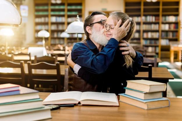 Nonno barbuto senior bello che abbraccia e bacia la sua nipote carina, bambina in occhiali, seduto al tavolo con molti libri nella biblioteca antica Foto Premium