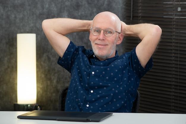 Uomo d'affari maggiore bello che si distende nell'ufficio Foto Premium