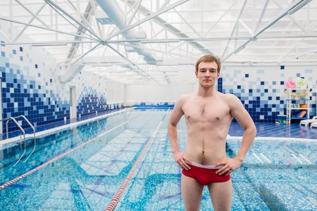 Bell'uomo senza camicia in piedi con le mani sui fianchi in piscina Foto Premium