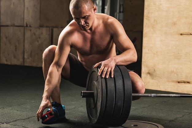Sollevatore di pesi bello che prepara per l'allenamento con il bilanciere Foto Premium