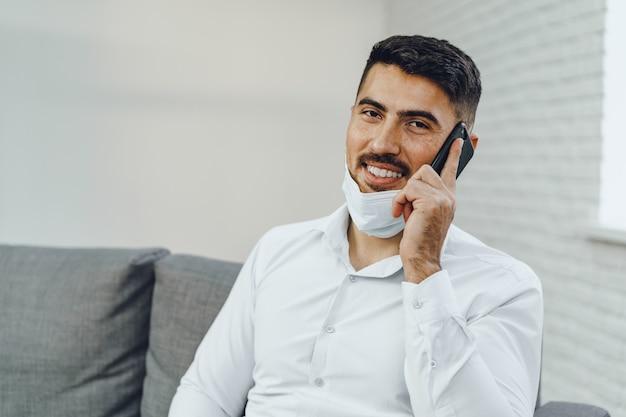 Bel giovane imprenditore con maschera facciale parlando al telefono, ritratto Foto Premium