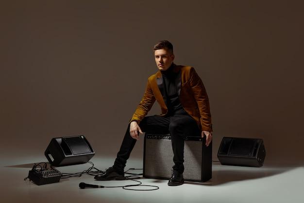Cantante di handsone in vestito che si siede su una colonna musicale Foto Premium