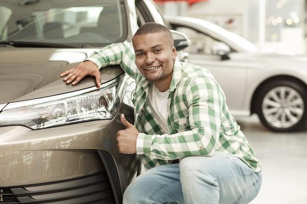 Uomo bello africano felice che mostra i pollici su che posano vicino alla sua nuova automobile al concessionario Foto Premium