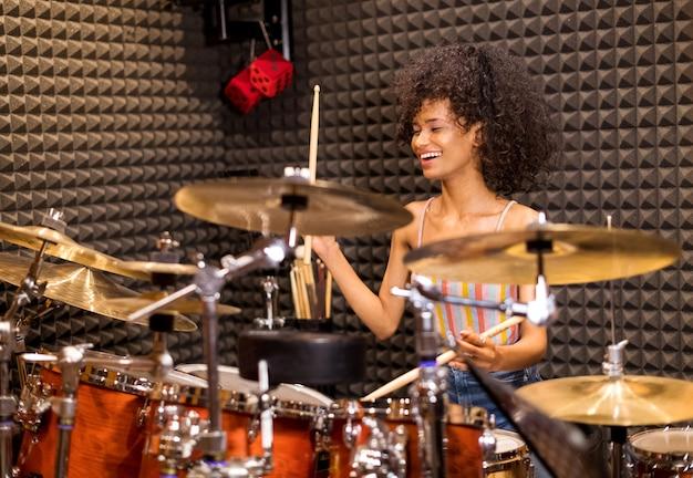 Felice donna afro-americana che suona la batteria e i piatti in uno studio Foto Premium