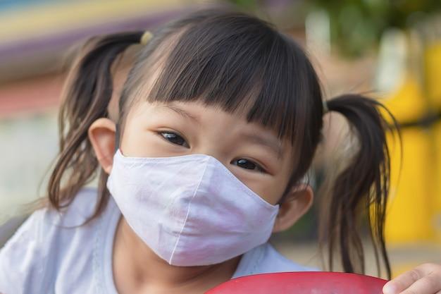 Ragazza asiatica felice del bambino che sorride e maschera da portare del tessuto Foto Premium
