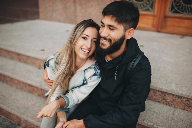 Felice uomo barbuto e donna allegra che abbraccia mentre è seduto sui gradini sulla strada Foto Premium