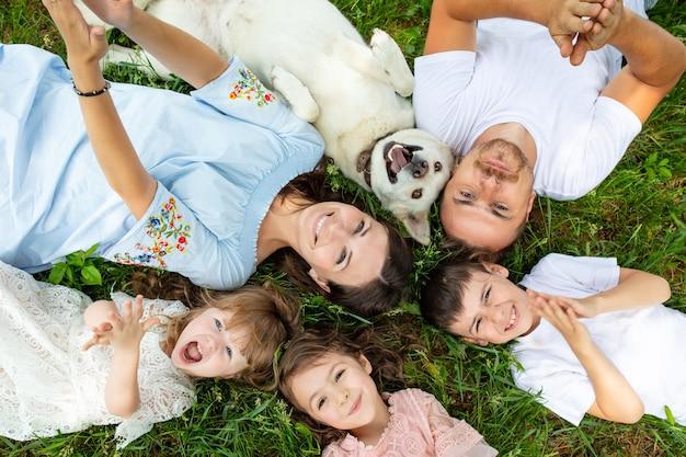 Felice bella grande famiglia insieme madre, padre, figli e cane sdraiato sulla vista dall'alto dell'erba Foto Premium