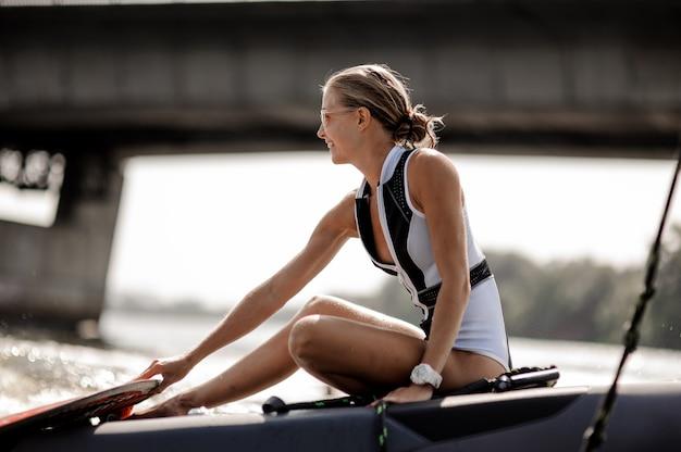 Bello costume da bagno felice della donna in bianco e nero che si siede su un wakeboard Foto Premium