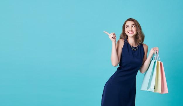 Bella giovane donna felice in vestito blu con i suoi sacchetti della spesa e dito della tenuta della mano che indicano su su blu-chiaro con lo spazio della copia. Foto Premium