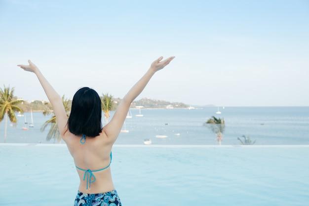 Bikini felice donna sulla piscina e mare nuvole cielo. Foto Premium