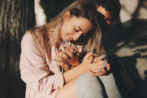 Felice donna bionda con uomo seduto vicino all'albero alla luce del sole che stringe a sé con amore Foto Premium