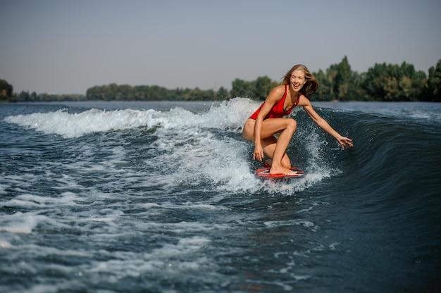 Surfista biondo felice della donna che guida giù l'onda di spruzzatura blu Foto Premium