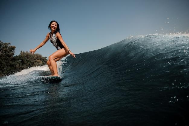 Donna felice del brunette che pratica il surfing a bordo giù l'acqua blu Foto Premium
