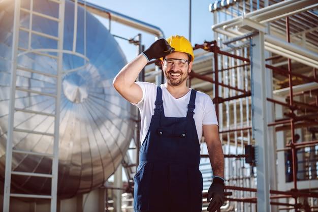 Lavoratore caucasico felice in generale e con il casco sulla testa che posa davanti al serbatoio dell'olio. Foto Premium