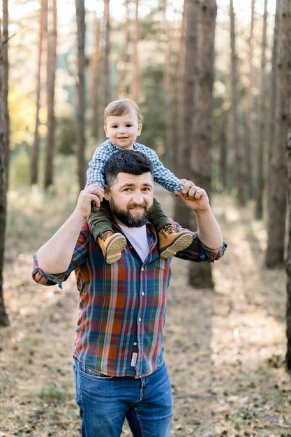 Felice famiglia allegra, bel padre barbuto e il suo piccolo figlio carino nel parco in autunno, giocando e ridendo Foto Premium