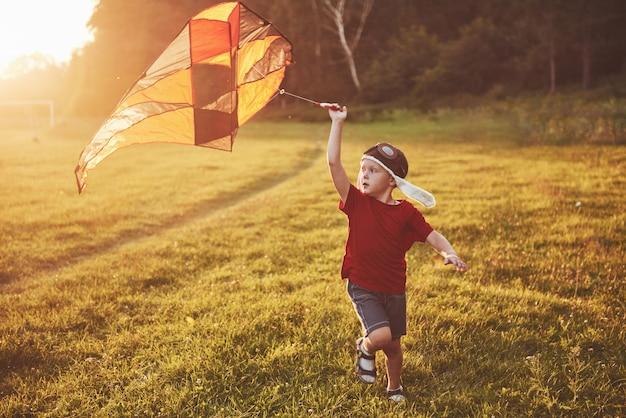 Il bambino felice lancia un aquilone nel campo al tramonto. ragazzino e ragazza in vacanza estiva Foto Premium
