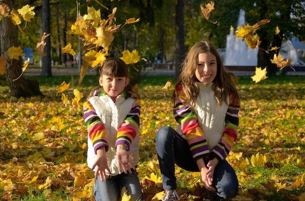 I bambini felici in autunno parcheggiano, i bambini attivi divertendosi e giocando con le foglie gialle all'aperto Foto Premium