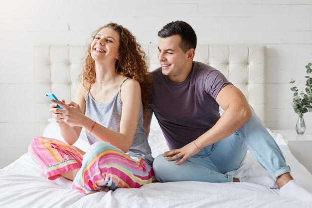 Le coppie felici trascorrono la mattinata in camera da letto, controllano i social network tramite smartphone, sono sempre in contatto, comunicano con i loro amici, famiglia con telefoni cellulari seduti a ridere nel comodo letto Foto Premium