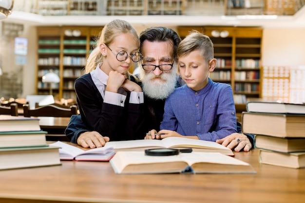 Felice anziano uomo barbuto, nonno e suo nipote carino e nipote sono seduti al tavolo nella vecchia biblioteca vintage e libri di lettura Foto Premium