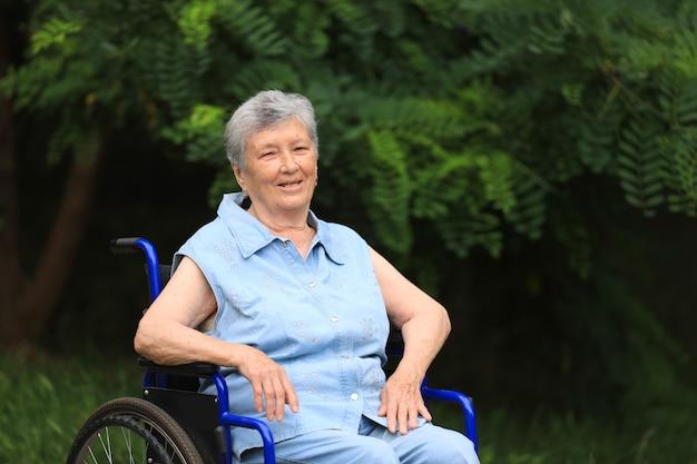 Felice anziani disabili donna seduta in sedia a rotelle all'aperto Foto Premium