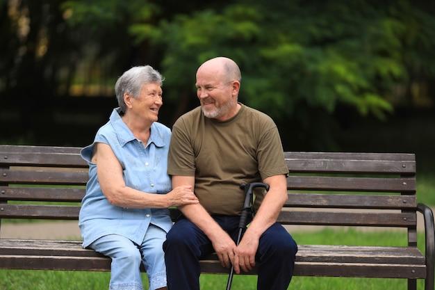 Felice l'uomo anziano e la donna disabile si siedono sulla panchina all'aperto nel parco estivo Foto Premium