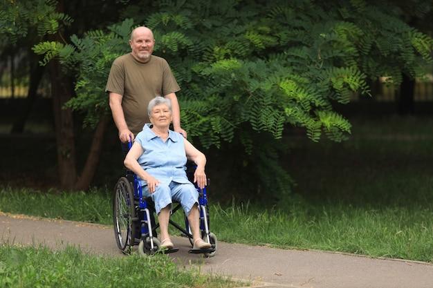 Uomo anziano felice che cammina con donna anziana disabile che si siede in sedia a rotelle all'aperto Foto Premium