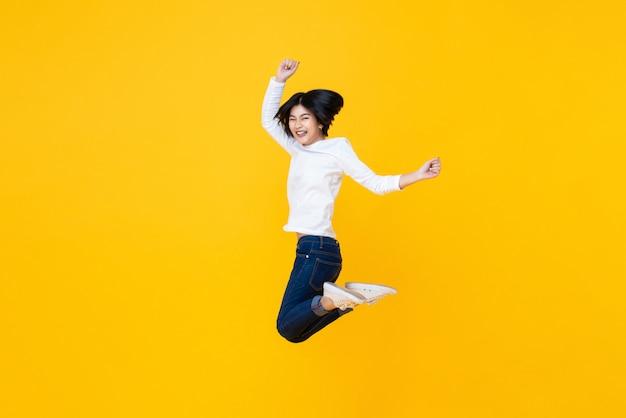 Felice donna asiatica energica saltando a mezz'aria Foto Premium