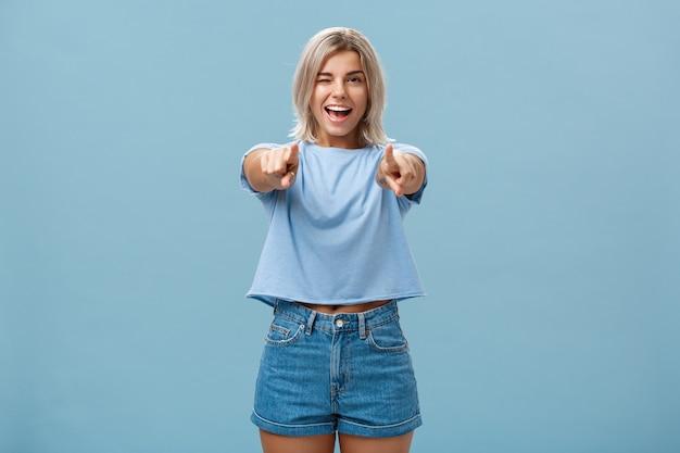 Felice, entusiasta, elegante, biondo, femmina, scegliere, o, fare, suggerimento, sorridente, con gioia, e, ammiccante, da, stupore, e, felicità, proposta, sopra, blu Foto Premium