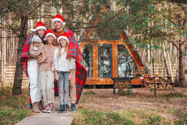 Famiglia di quattro felice in cappello della santa che gode delle vacanze di natale. genitore con bambini avvolti in una coperta Foto Premium