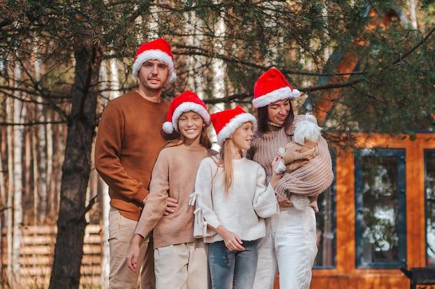Famiglia di quattro felice in cappello della santa che gode delle vacanze di natale Foto Premium