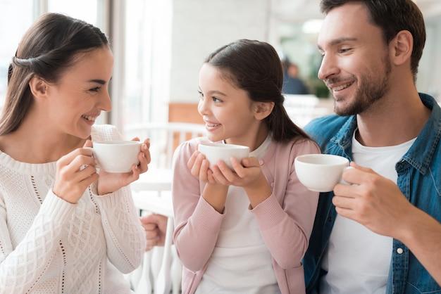 La famiglia felice ha il caldo inverno tein cozy cafe. Foto Premium