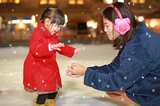La madre felice della famiglia e la bambina adorabile ha un divertimento in neve, orario invernale. Foto Premium