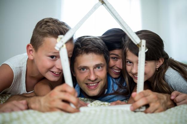 Famiglia felice che gioca con la casa di modello in camera da letto Foto Premium