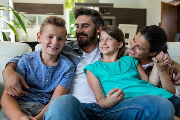 Famiglia felice che si siede con il braccio intorno sul divano Foto Premium