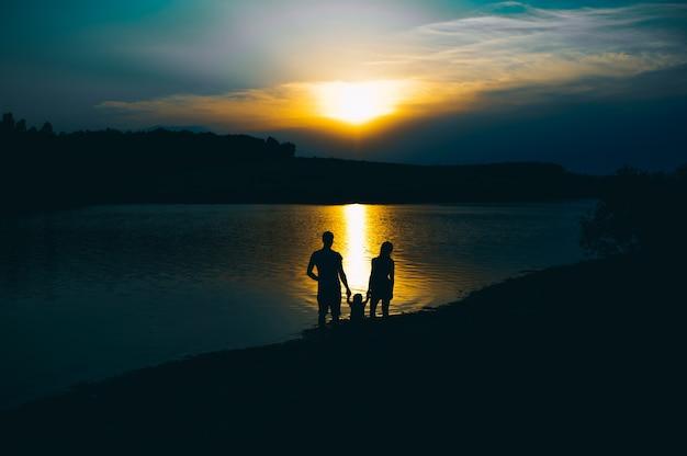 Famiglia felice insieme, genitori con il loro piccolo bambino al tramonto. padre, alzando, bambino, in, aria. Foto Premium