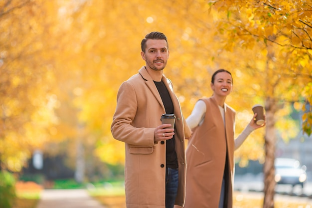 Famiglia felice che cammina nella sosta di autunno sulla giornata di sole autunnale Foto Premium
