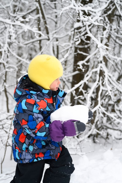 La famiglia felice con i bambini si diverte a trascorrere le vacanze invernali nella foresta invernale innevata. ragazzino ragazzo gioca allegro Foto Premium
