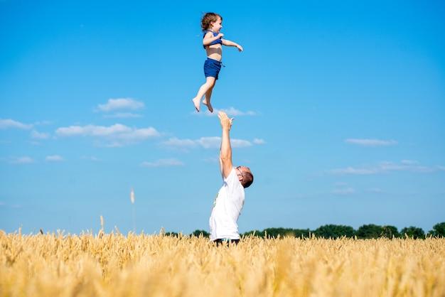 Padre felice in piedi in mezzo al campo lanciando suo figlio che indossa cappelli pantaloncini e magliette il giorno d'estate su sfondo blu cielo Foto Premium