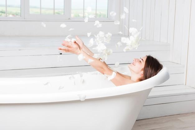 Petali di lancio femminili felici che si trovano nella vasca da bagno Foto Premium